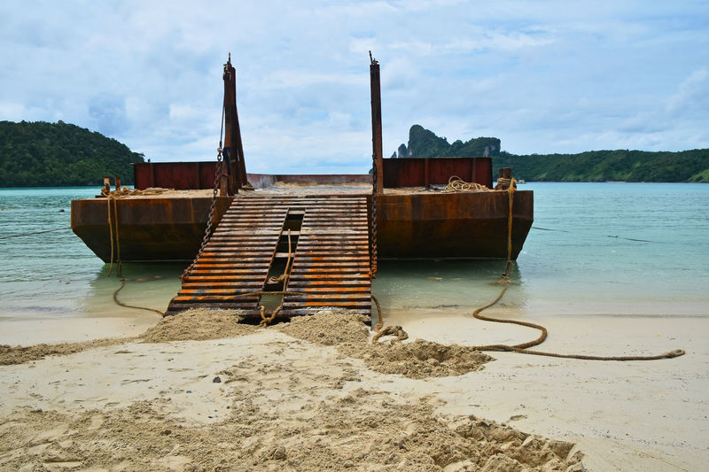 Old rusty corroded cargo barge in the bay ofPhi Phi Don island Ark Barge Beach Cargo Corrosion Ferry Industrial Island Landscape Landscapes With WhiteWall Load Old Phi Phi Ramp Rusty Sand Sea Seashore Ship Spotted In Thailand A Bird's Eye View