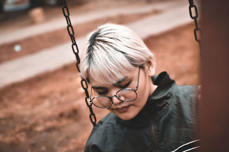 Close-up of woman sitting on swing at playground