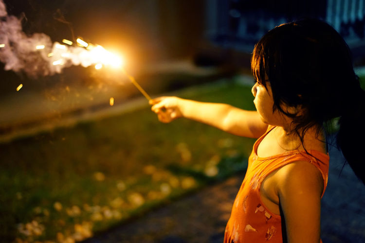 Girl holding illuminated sparkler at night