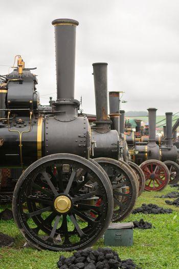 Vintage steam engines on field against sky