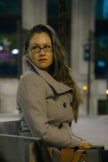 Young Woman Looking Away While Sitting Against Buildings At Night