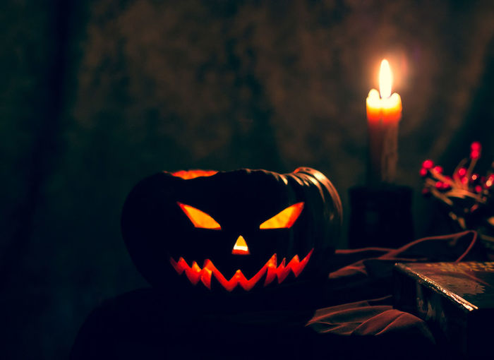 Halloween pumpkin on a black mystical background. burning candles, a symbol of the autumn holiday.