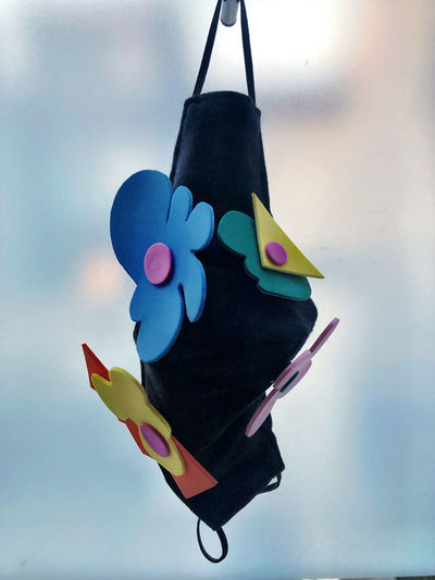 Close-up of multi colored toy hanging on paper