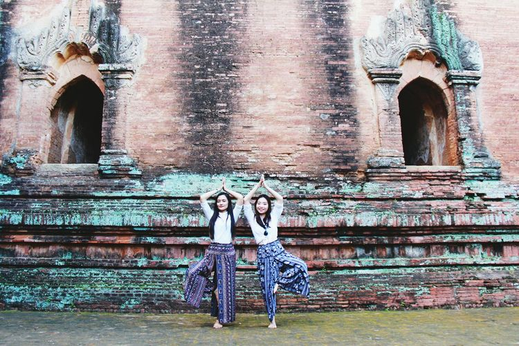 Female Friends Practicing Tree Pose Against Old Wall