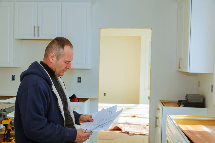 Man reading blueprint while standing at home