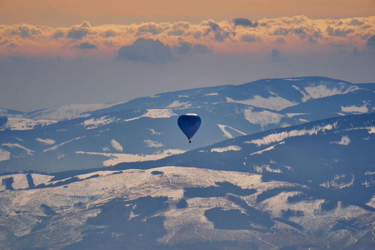 Aerial view of hot air balloon flying over mountains against sky