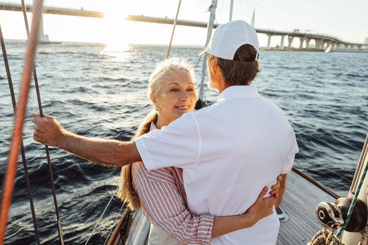 Happy senior couple sailing in sea