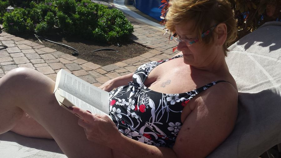 Senior Woman Reading Book While Lying On Lounge Chair
