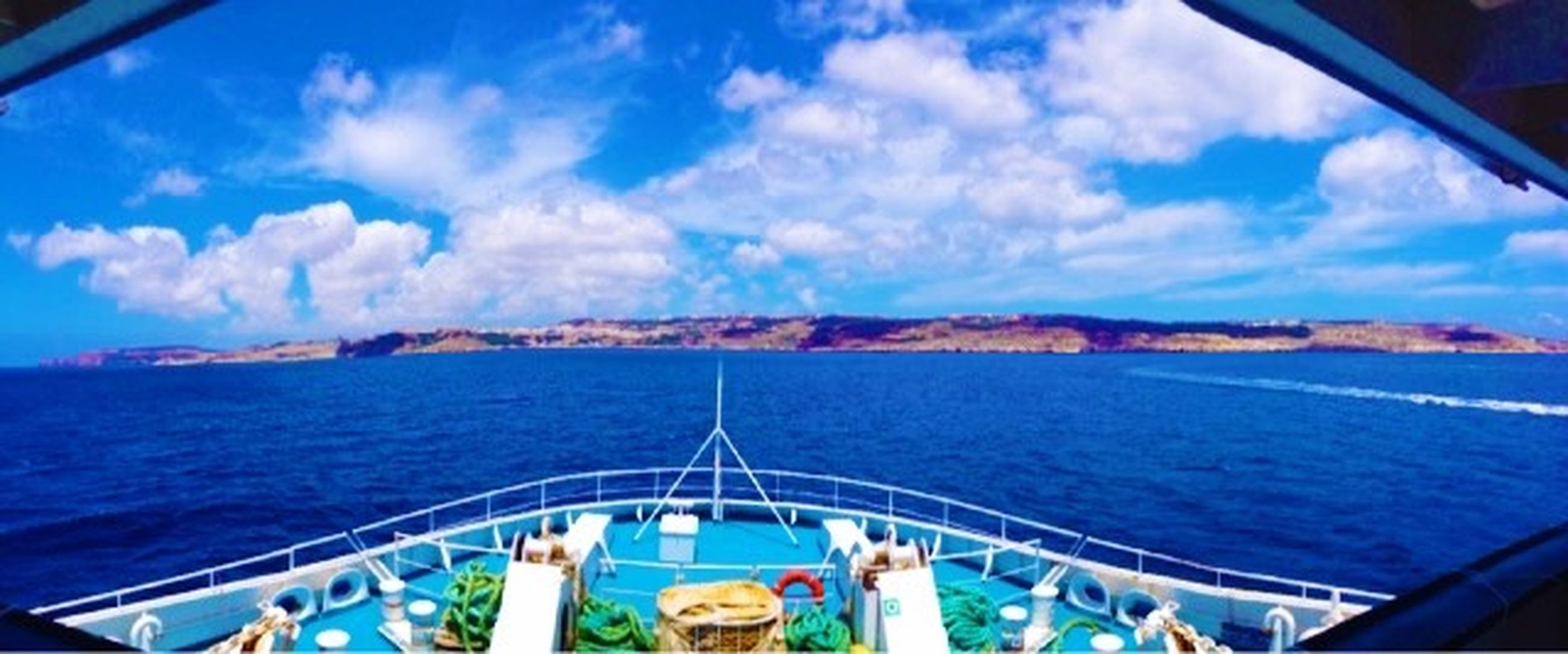 sea, water, sky, nautical vessel, transportation, blue, cloud - sky, vacations, mode of transport, leisure activity, scenics, boat, lifestyles, travel, cloud, mountain, tourism, nature, beauty in nature
