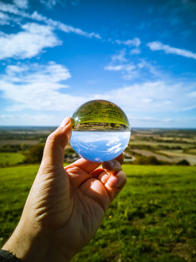 Cropped hand holding crystal ball against landscape