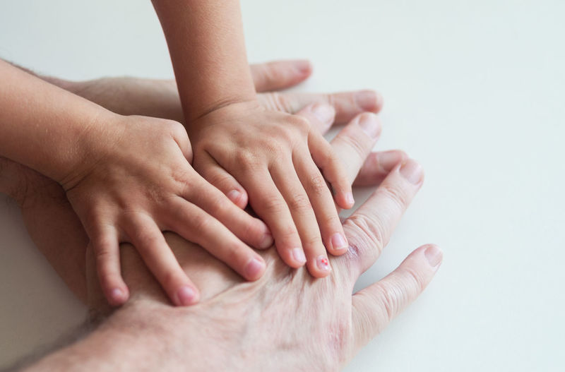 Cropped image of family hands stacking on white table