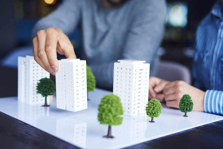 Midsection of business people discussing over architectural model