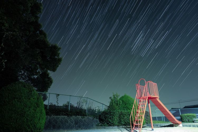 Low angle view of slide against meteor showers at night