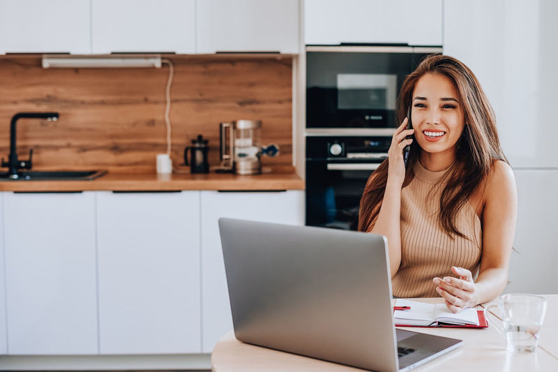 Portrait of smiling woman using mobile phone at home