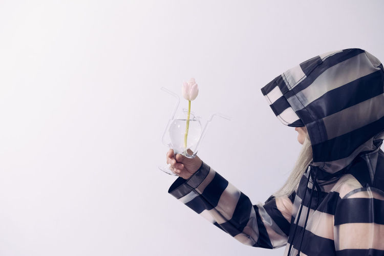 Side view of woman wearing raincoat while holding tulip in glass vase against white background