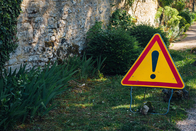 Road sign by wall