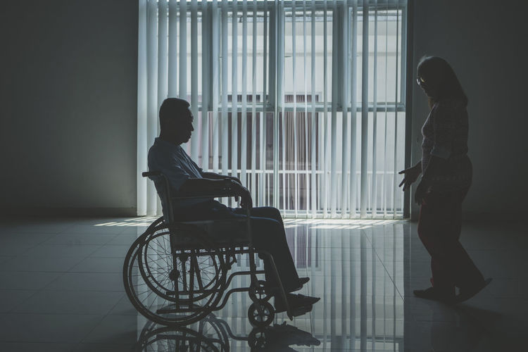 Woman by man sitting on wheelchair