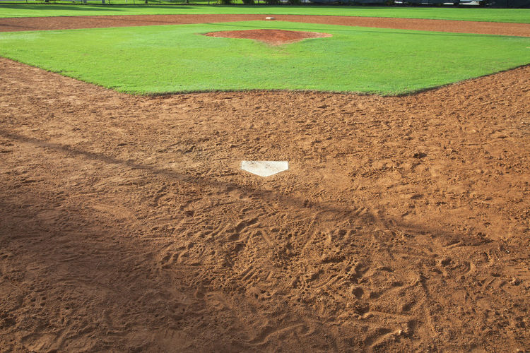 View of a baseball field from behind home base Baseball Field Dirt Grass Green Color Sport Sunlight Youth Outdoors No People Photography Infield Home Plate Home Base Mound Pitcher Behind