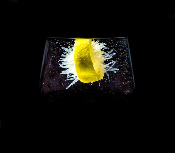 Close-up of lemon on glass against black background