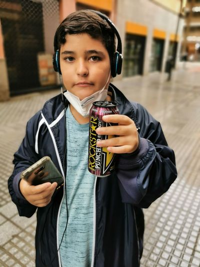 Portrait of boy holding camera while standing outdoors