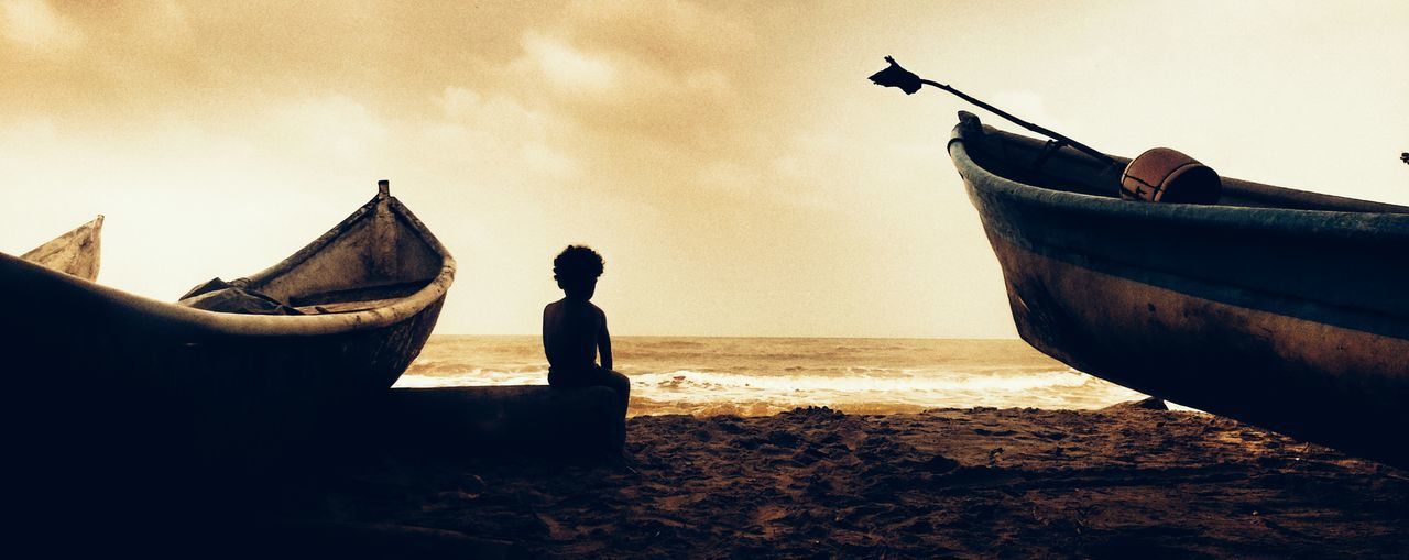 Rear View Of Child And Boats On Beach