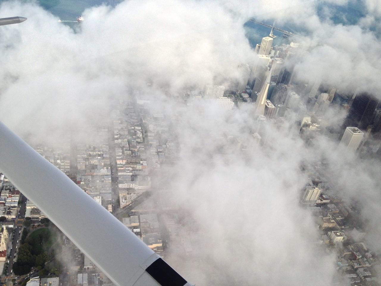 Cropped image of airplane over clouds covering cityscape