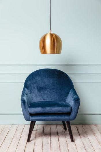 Empty chair on hardwood floor against wall