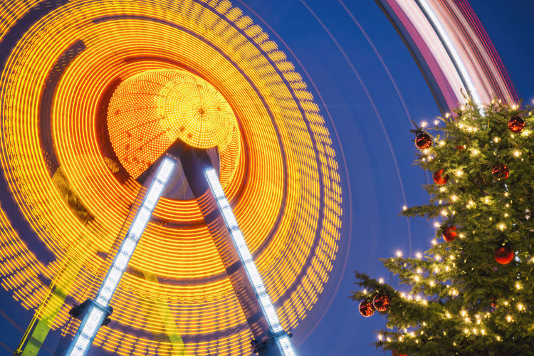 Low Angle View Of Spinning Ferris Wheel By Fernsehturm Tower During Christmas