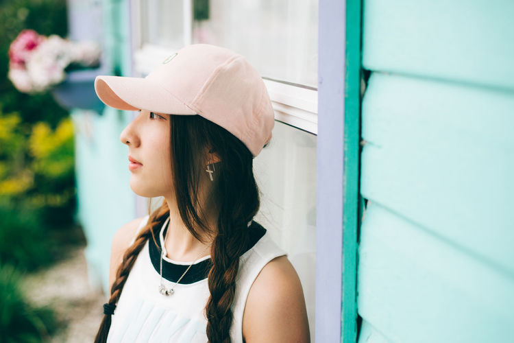 Thoughtful woman wearing cap by wall