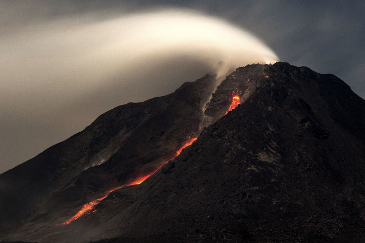 Close-up of volcanic mountain against sky at night