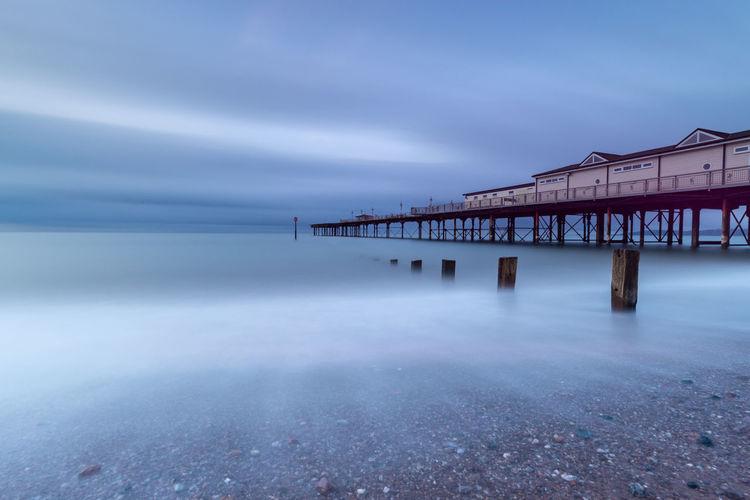 Pier over sea against sky at dusk