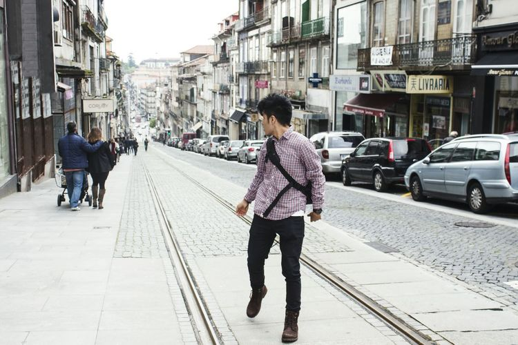 Man Looking Back While Walking On Street In City