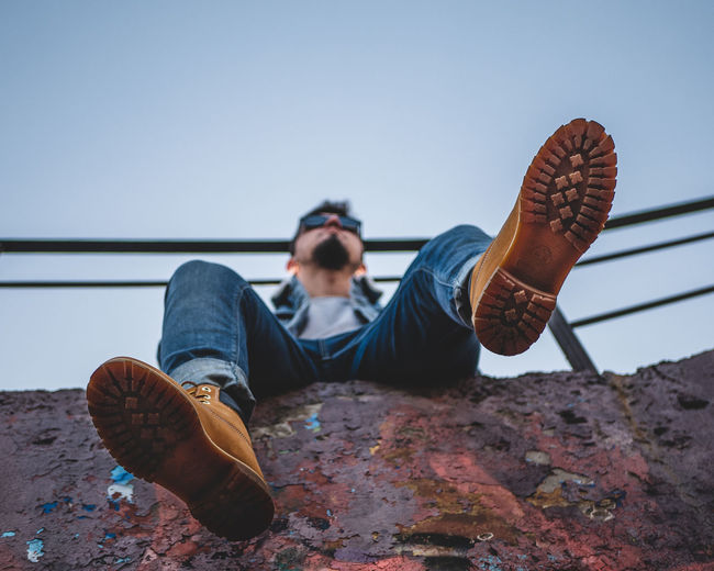 Low section of man relaxing against clear sky