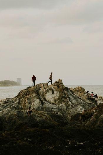 Men on rocky shore against sky