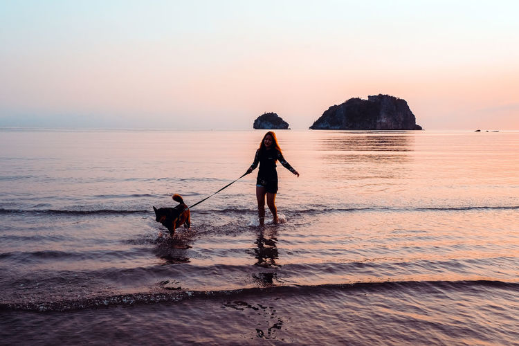 Silhouette mid adult woman with dog standing at beach against sky during sunset