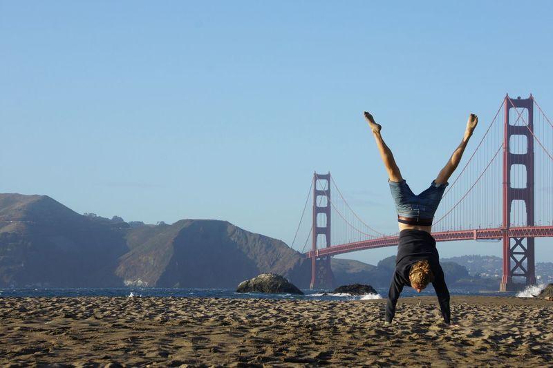 Man doing handstand on beach against clear sky