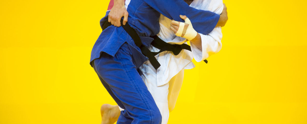 Midsection of people practicing martial arts against yellow background