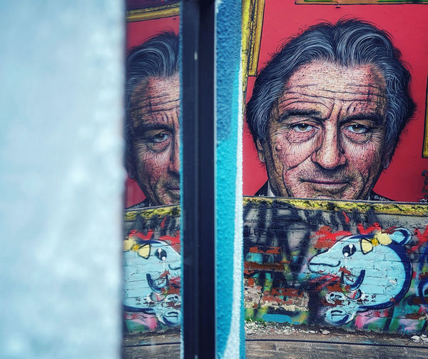 Portrait of man standing against graffiti