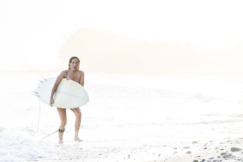 Portrait of woman with surfboard walking at beach