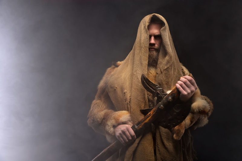Midsection of man holding wooden axe against black background