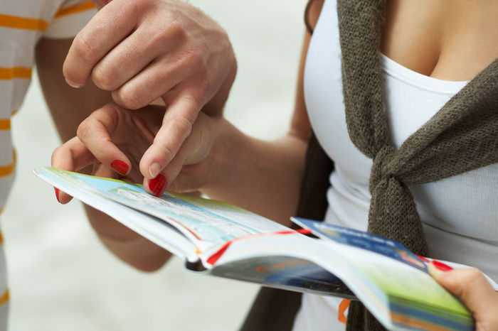 Couple reading map in tourist guide Close-up Couple Directions Guide Human Hand Looking Map Maps People Pointing Searching Tourist Tourist Guide Travel Trip Young Women