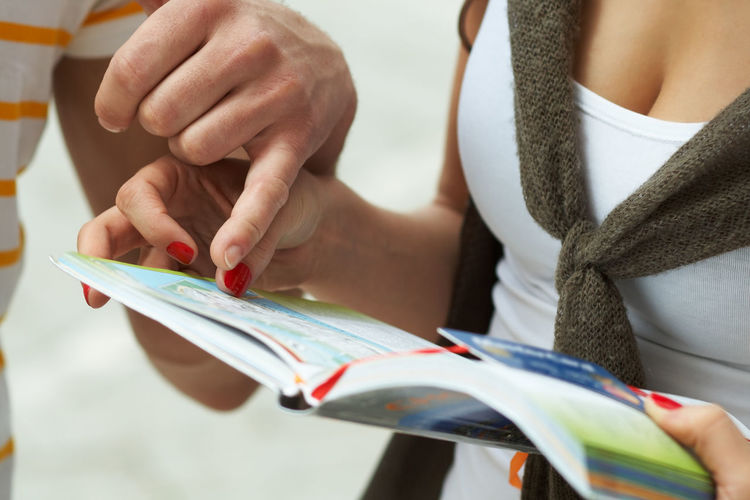 Midsection Of Man Showing Map To Woman Holding Book With Credit Card