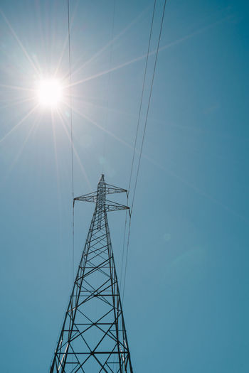 High Voltage Electricity Pylon/Pole Sun Star Blue Bright Sun Cable Clear Sky Connection Day Electricity  Electricity Pylon Fuel And Power Generation High Voltage Power Line Low Angle View No People Outdoors Power Line  Power Pole Power Supply Sky Sunlight Technology