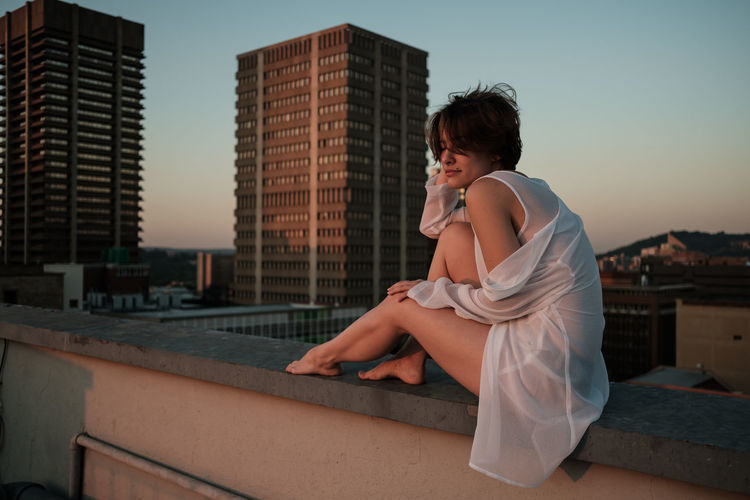 Young woman sitting on retaining wall in city against sky during sunset