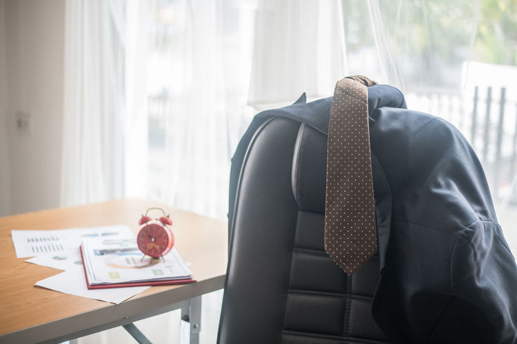 Close-up of necktie and blazer on chair in office