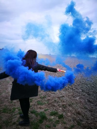 Rear view of woman holding distress flare on field