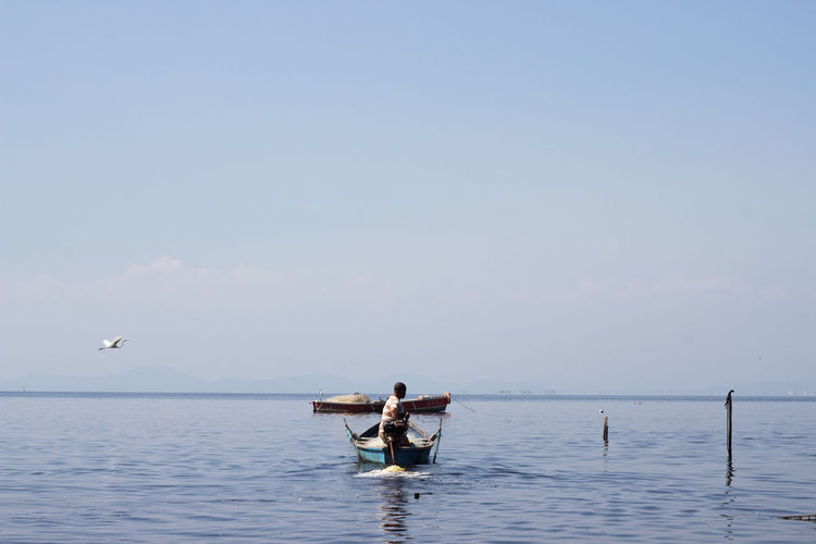 Fisherman fishing in sea against blue sky