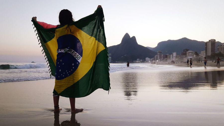Rear view of girl holding brazilian flag while standing at beach against clear sky
