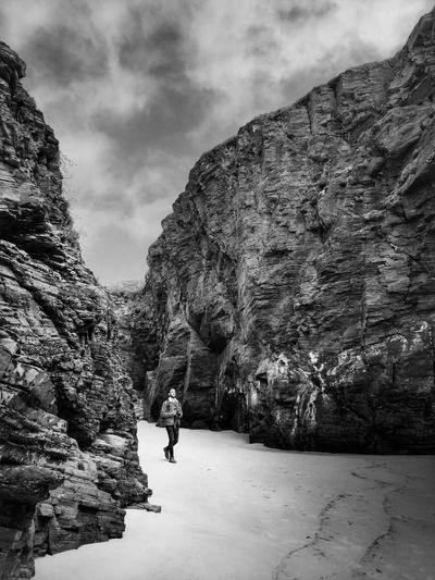 Man walking on rock by mountain against sky