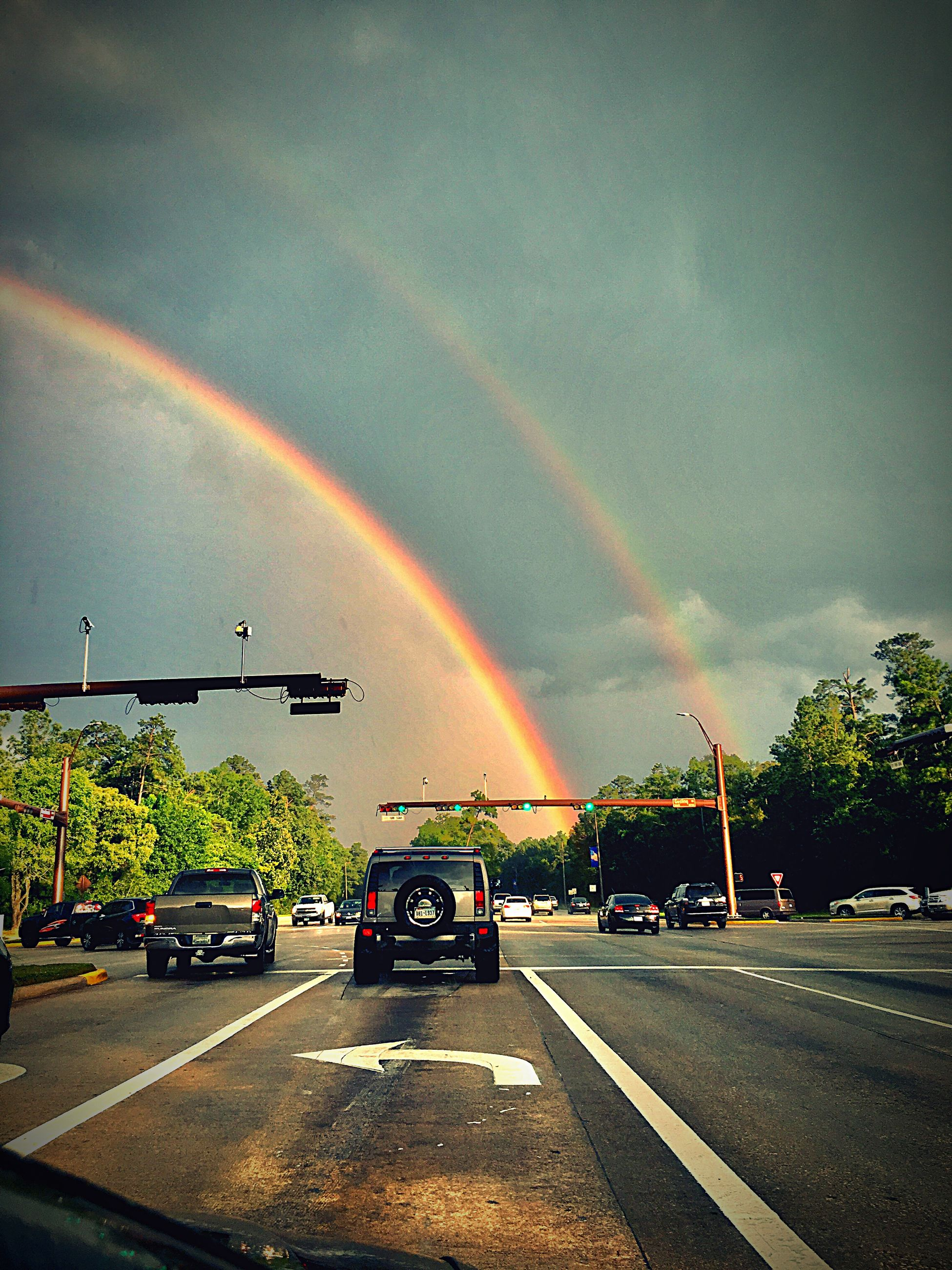 rainbow, double rainbow, weather, storm cloud, cloud - sky, mode of transport, transportation, no people, outdoors, storm, nature, car, beauty in nature, scenics, tree, road, multi colored, sky, day, built structure, thunderstorm, building exterior